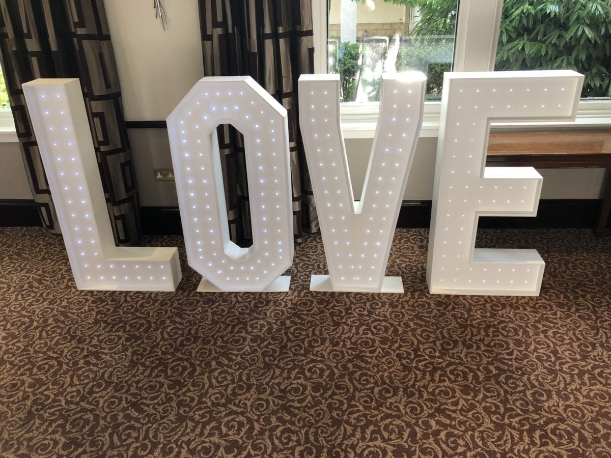 "4ft tall giant letter hire saying ""LOVE"". You could hire this with our white led dance floor as part of our £1,000 deal at your venue in Gretna Green."